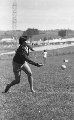 A Maori girl photographed as she pitches a softbal...