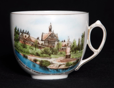 This white china souvenir ware cup features an ima...