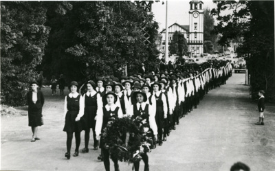 A large parade of girls wearing school uniform is ...