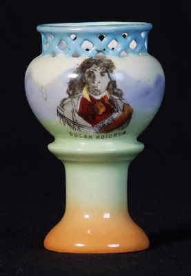This souvenir ware china egg cup is mounted on a c...