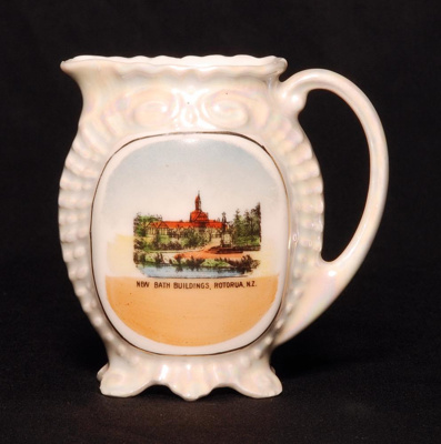 A small pearl white china souvenir milk jug with a...