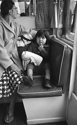A small girl sits on a seat waiting for the trip t...