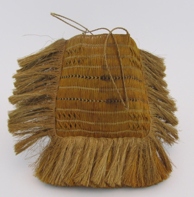 Has 2 plattted flax straps. Parts of the kete have...