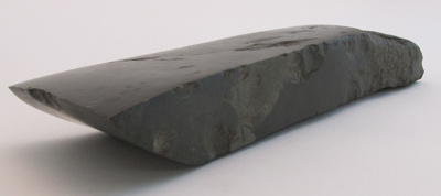 Dark grey toki (adze). Triangular in shape with fl...