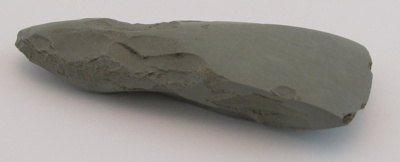 Pale grey stone toki (adze). Triangular in shape. ...