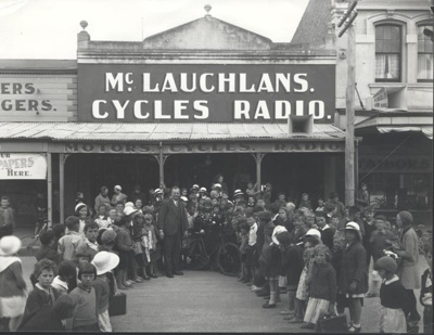 McLaughan's Cycle Shop and the Woman in Red., Clarke, C.E   Waimate New Zealand, 1936, 011-2002-1026-00874