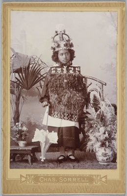 Untitled [Maori girl with parasol, cloak and crown]