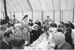 Photo: Jack Phillips, Manager of the 1949 New Zealand Cricket Team, and guests, enjoying lunch in a marquee during the traditional fixture against the Maori CC., Worcester Park, Surrey, 5.5.1949;...