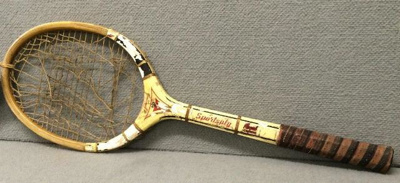 A wood-framed tennis racket, donated by W M (Arch)...