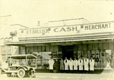 Mounted Photograph of R.T.Bullock's First Motorised Delivery Van outside the Cash Merchants Store in Princes St opposite the Memotial Arch. Taken about 1921.; H.J.Finlay.; 2013.075