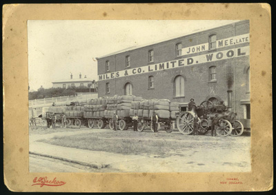 [Traction engine with four wagons loaded with wool bales outside Miles & Co Limited, Timaru]; 1895-1915; 1828