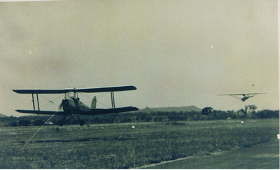 Photograph - Tiger moth aircraft towing a glider at Oakey, Queensland.; 1944; 6854