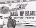B&W photograph of two males standing next to sign advertising site for ASHOF pre-1988.; pre-1988; 16606