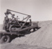 B&W Photograph of Ken Peters driving tractor off flat bed truck onto dirt embankment. ; c 1950; 18363