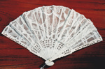 White, lace-like, folding hand fan. ; 1995; 19889