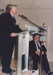 Photograph - Colin Munro addresses the audience at the Dame Mary Durack Outback Art and Craft Awards with Ranald Chandler looking on.  ; Exposure Photographers; 2003; 19202