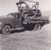 B&W Photograph of male standing at front of tractor on flat bed truck, ready for unloading  Dirt in background.   ; c 1950; 18362