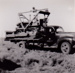 B&W Photograph - Male standing on machinery (TD35(?) on back of flat bed truck.  Open field in background.  ; c 1950; 18360