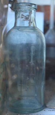 Bottle, glass, used to measure milk quality, used at Elmgrove Cheese Factory prior to 1929
