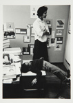 [Untitled, boy laying on a box in classroom, with teacher standing nearby]. ; Heron, Reginald; 1966; 1972:0154:9999