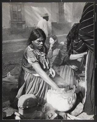 Tarascan Indian woman preparing food for Pal Sunday Fiesta on the second class bus plaza in Patzcuaro, Michocan, Mexico; Webb, Todd; 1966; 1982:0091:0001