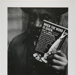 Untitled, [Man holding a glass drink bottle and a book of social commentary]. ; McLoughlin, Mike; 1964; 1974:0023:0001