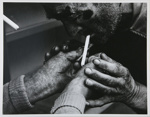 Untitled, [Man lighting a cigarette].; McLoughlin, Mike; c. a. 1970; 1974:0023:0004