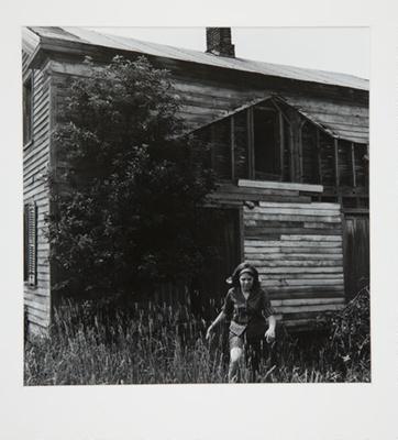 [Woman walking through field in front of wooden house]; Fichter, Robert; ca. 1966; 1971:0030:0001