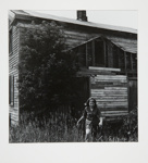 [Woman walking through field in front of wooden house]; Fichter, Robert; ca. 1966; 1971:0030:0001