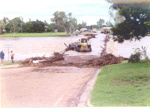 Council workers clearing debris off flooded bridge, Hughenden 2002; Unidentified; ca. 2000s; 2012-75