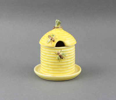 Honey pot; a yellow china honey pot shaped as a be...