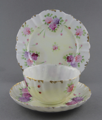 Cup, saucer and plate set. It has a pattern of bun...