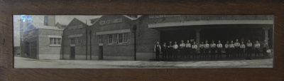 A black and white panoramic photograph of 18 male ...