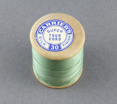 Sewing thread on wooden spool; holding super four ...