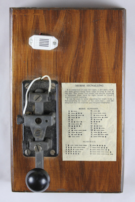 Morse code key; on a wooden base. It was made by I...