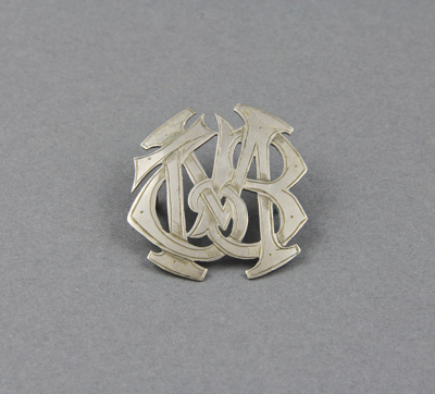 A silver hat badge with entwined initials, MTB, is...