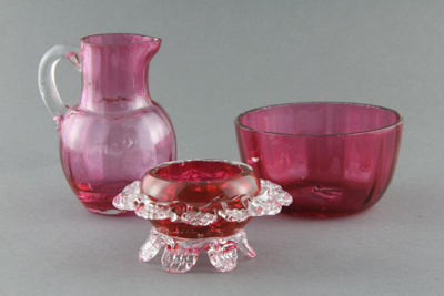 Glass ware; a red sugar bowl with matching cream j...