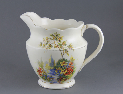 Jug; a white jug with gold gilding and two decals ...