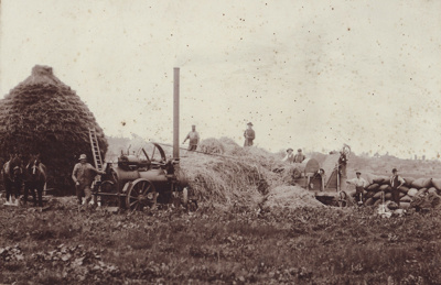 A black and white photograph of a threshing mill c...
