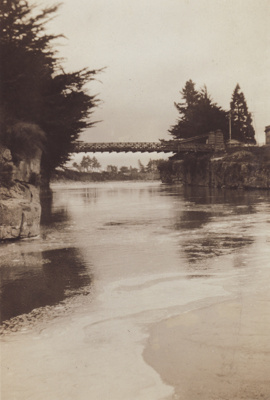 A black and white photograph taken from river leve...