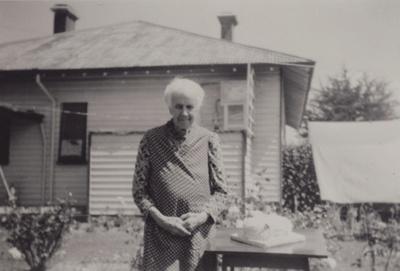 A black and white photograph of Mrs Hewlett standi...