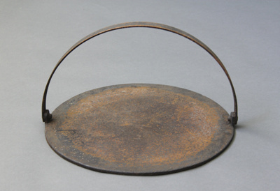 Griddle; a round black cast iron griddle with hand...
