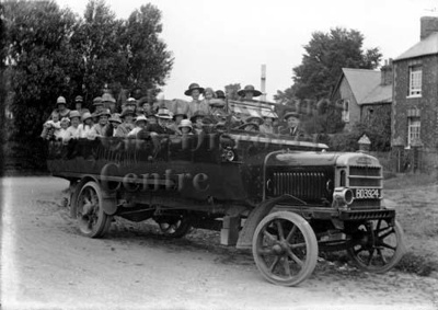 A large group of people sitting in the back of a charabanc vehicle, parked in front of the Bow Brickhill war memorial.