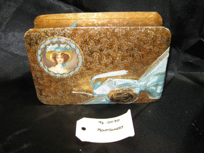 """Chocolate Box: """"Chocolate Surfin Pascall"""", a gold embossed chocolate box with a blue ribbon and bow.."""