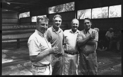 Four men standing in shed enjoying a drink; Unknown; 1998; CCPDM96