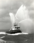 Photograph of a tug named 'Ganges' demonstrating her firefighting hoses; SHHMG:A2393