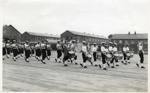 Photograph of HMS Ganges Bugle Band marching past on the parade ground in 1955.; photographer : Fisk, R A, Mr; SHHMG:A573
