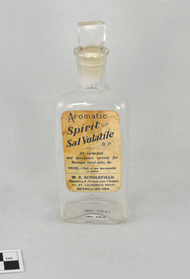 A Small Clear Glass Bottle With Matching Glass Closure and Paper Label: Aromatic Spirit of Sal Volatile; W E Scholefield, Dispensing and Photographic Chemist, Bexhill; c. 1920s; 2007.070