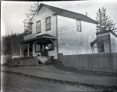 Mayne Island Store (Aitken's) with person standing on deck; Aitken, John; 2017.1.028