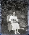 Woman sitting in a wicker chair, holding a book; Aitken, John; 2017.1.095